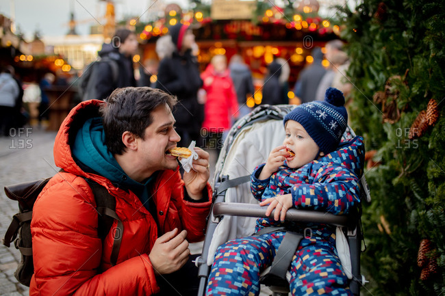 Father and son eating waffles at a Christmas market
