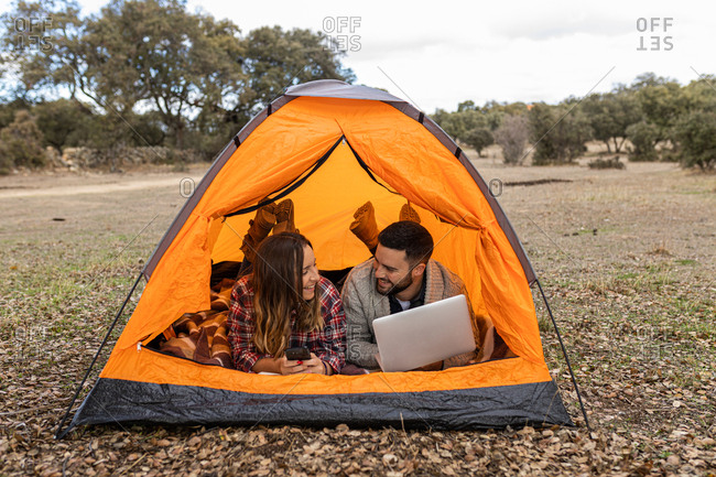Young couple camping in their tent, using laptop and smartphone