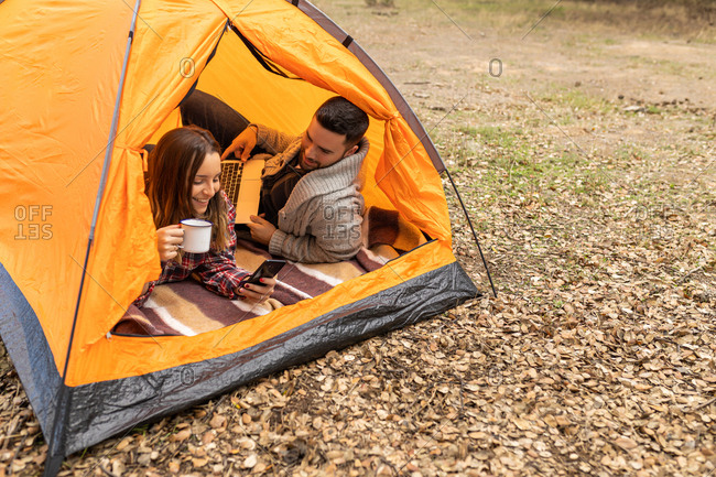 Young couple camping in their tent, drinking coffee and using laptop