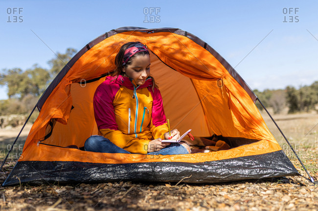 Young camping woman sitting in her tent, writing in her notebook