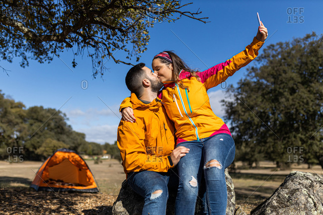 Young camping couple sitting on a rock taking selfies with their smartphone