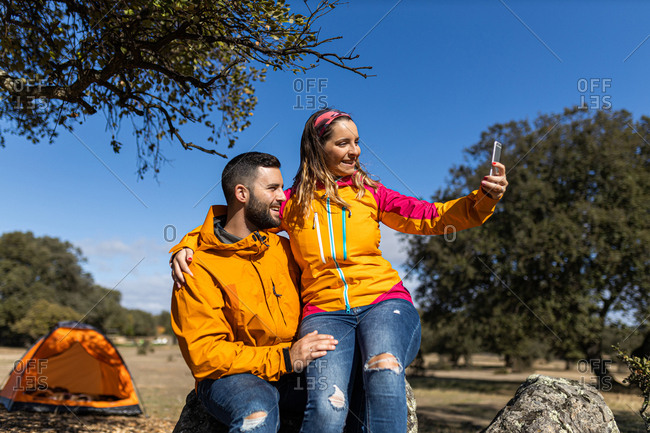 Young camping couple sitting on a rock taking selfies with the smartphone