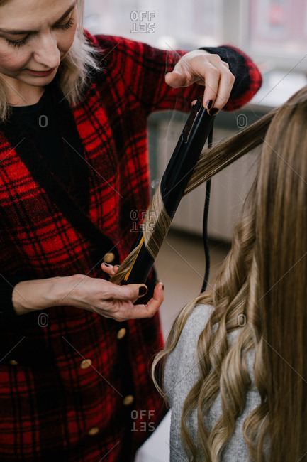 Hairdresser curling woman's hair