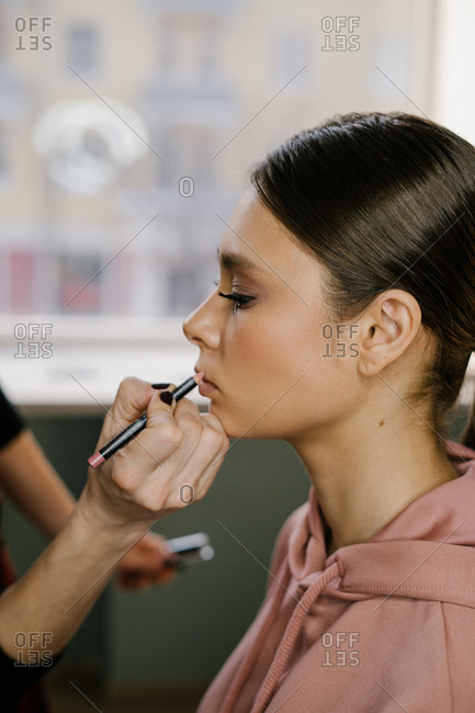Stylist outlining woman's lips with a pink pencil