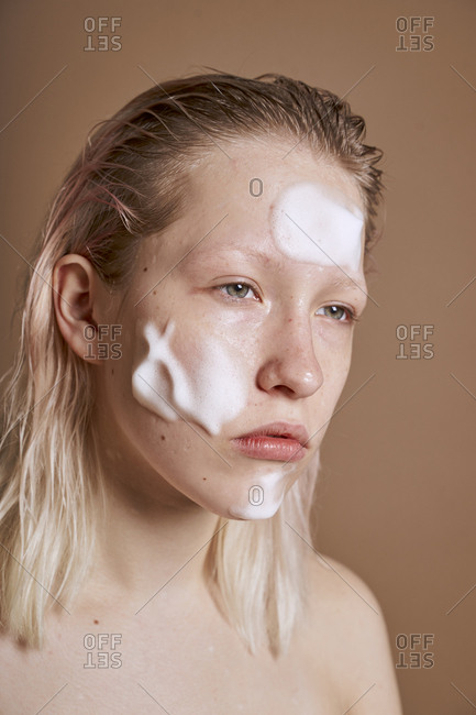 Young woman with cleansing foam on her face