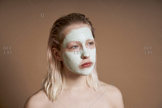 Woman using face mask for skin cleansing and moisturizing