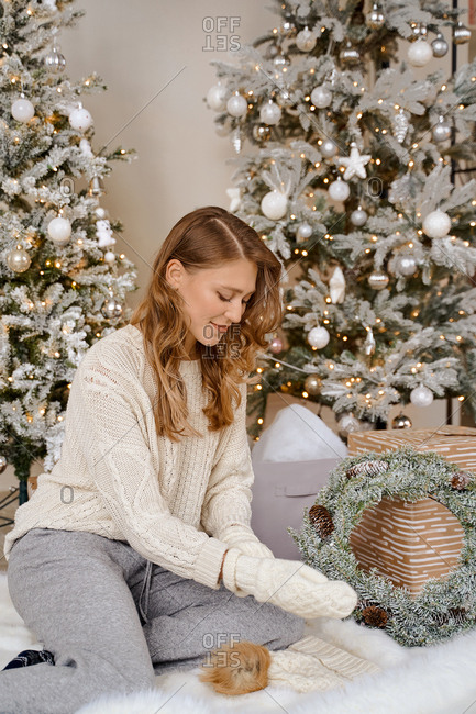 Christmas woman sits on the floor against the background Christmas tree and holds a Christmas wreath