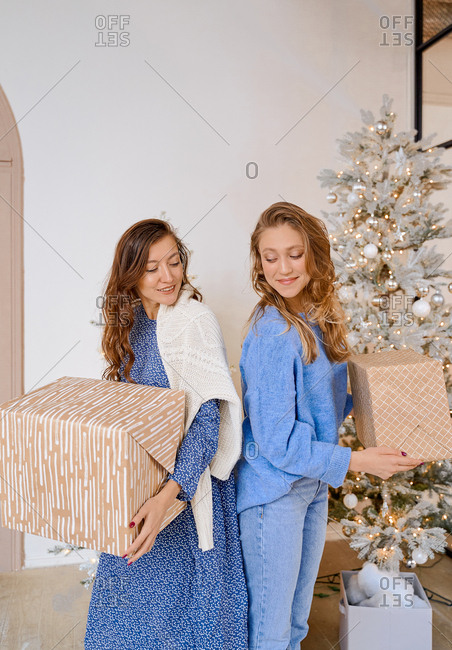 Two women in blue are holding gifts in front of the Christmas tree