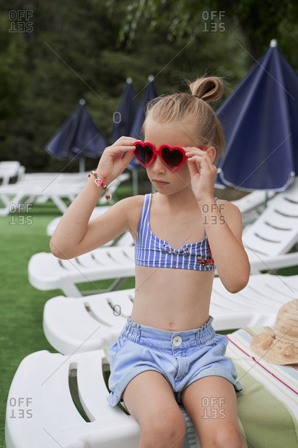 Girl puts sun protective glasses in the form of hearts at the pool