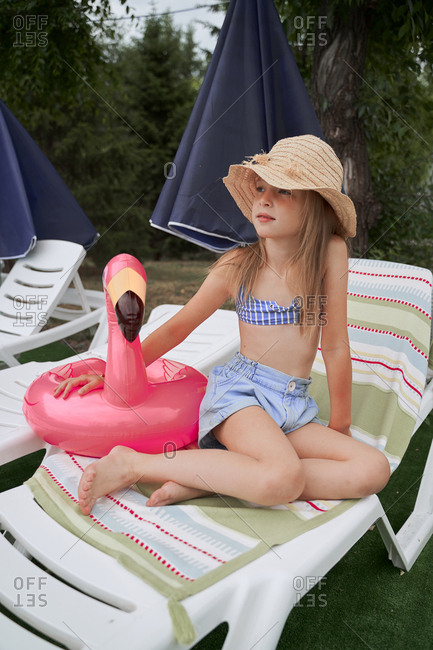 Girl in a swimsuit and panama hat with a flamingo float at the pool