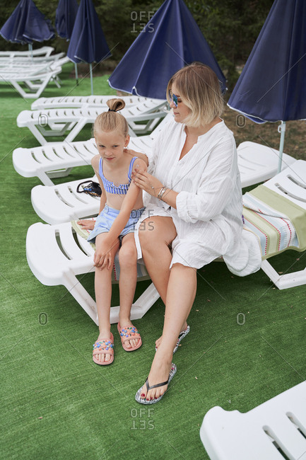 Woman spreads sunblock on her daughter near at the pool