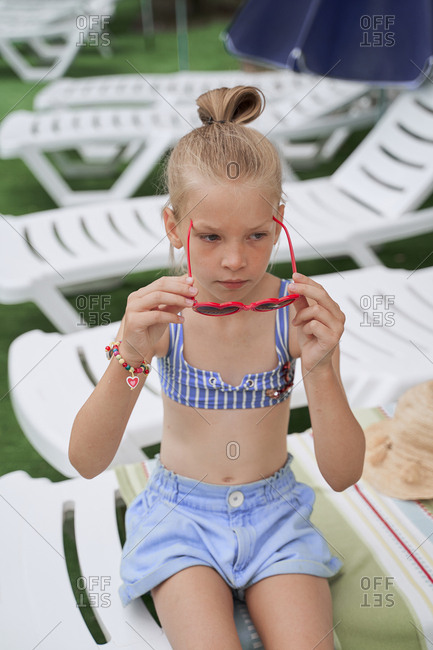 Girl puts on sun protective glasses in the form of hearts