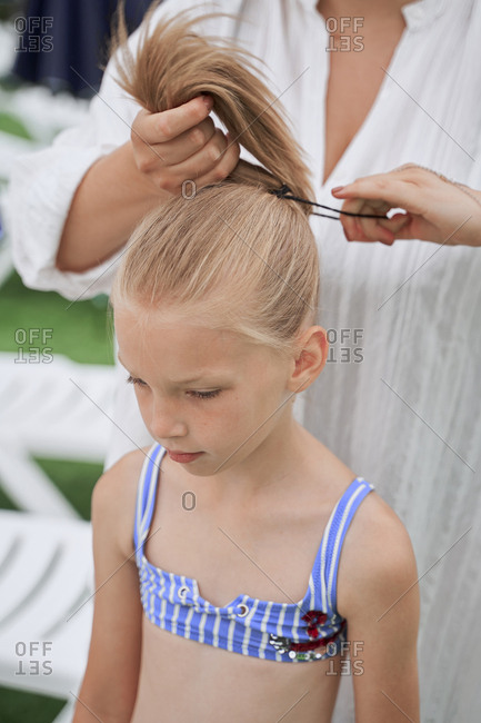 A woman in a tunic ties her daughter's hair in a ponytail at the pool