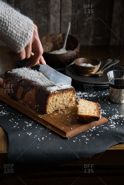 Hand slicing a coconut pound cake glazed with chocolate and coconut rasp