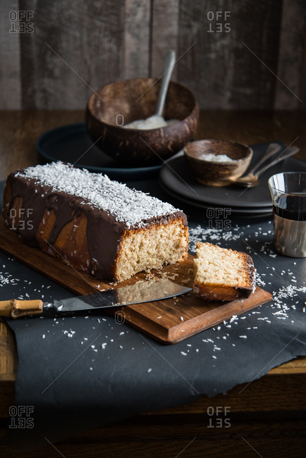 A coconut pound cake glazed with chocolate and coconut rasp ready to be shared