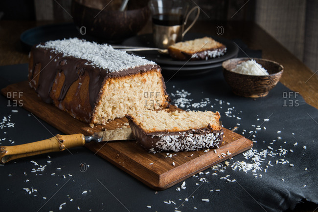 A coconut pound cake glazed with chocolate and coconut rasp sliced and ready to be shared