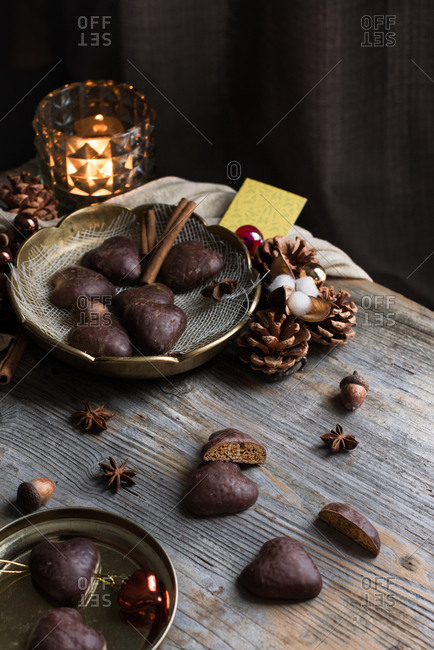 Lebkuchen hearts cookies covered in a dark chocolate glaze on a gold plate in a Christmas scene