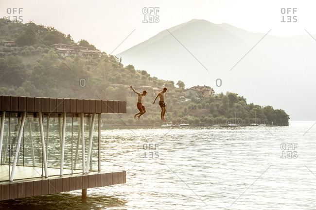 Iseo Lake, Italy - June 25, 2019: Guys jumping from an abandoned building along the lake near Pilzone