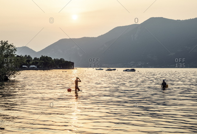 Iseo Lake, Italy - June 25, 2019: Tourists in the lake at sunset with boats in the distance