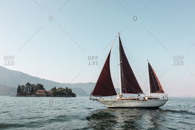 Iseo Lake, Italy - June 27, 2019: Sailing with a traditional wooden sailing boat