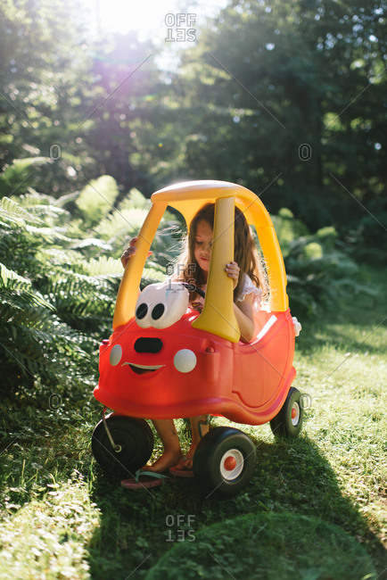 Girl riding in a plastic toy car