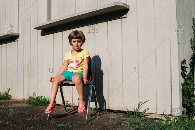 Young girl sitting in a plastic chair by a building making a silly face