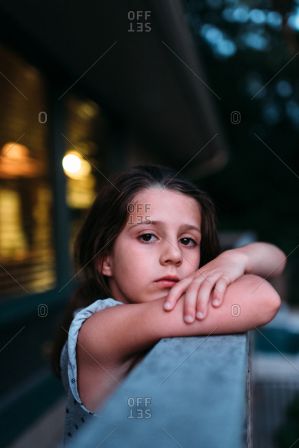 Portrait of a girl leaning on a deck railing at dusk
