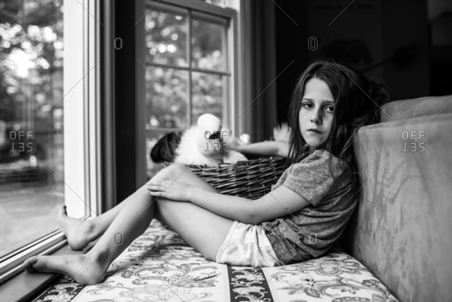 Portrait of a girl holding a stuffed animal by a window