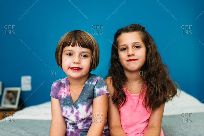 Portrait of two girls wearing red lipstick against a blue wall