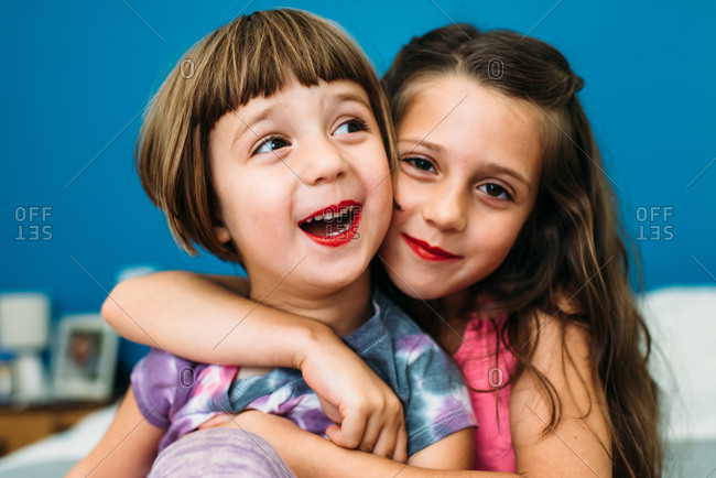 Portrait of two smiling girls wearing red lipstick and hugging