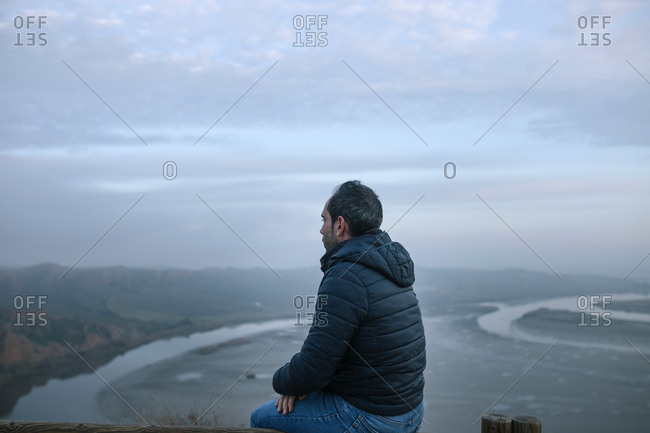 Young man up on a hill looking at the landscape