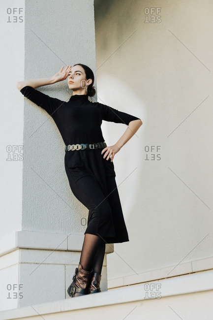 The young beautiful brunette wearing a black dress and massive earrings is posing in a modern urban location