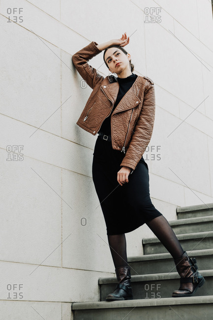 The young beautiful brunette wearing brown leather biker jacket is posing in a modern urban location