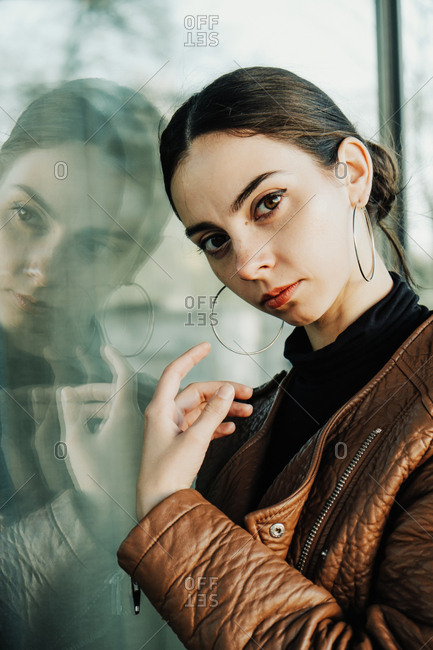 The young beautiful brunette wearing brown leather biker jacket is posing in a modern urban location with reflection