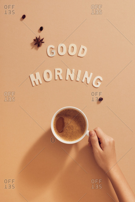 Hand holding cup of coffee under Good Morning sign