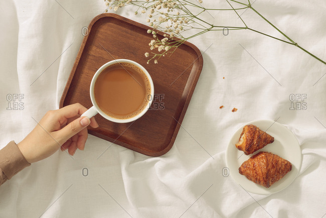 Woman's hands holding worm coffee cup. View from top