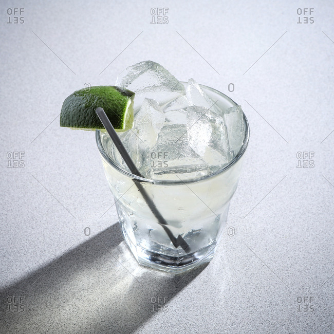 Gin and tonic cocktail on gray background.