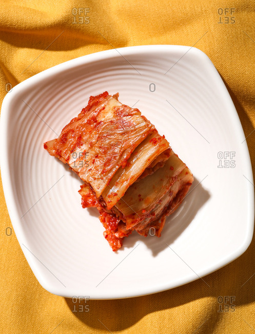 Kimchi served on plate on yellow background.