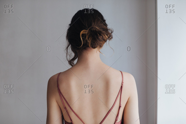 Back view of beautiful tender young woman in silky nightgown.