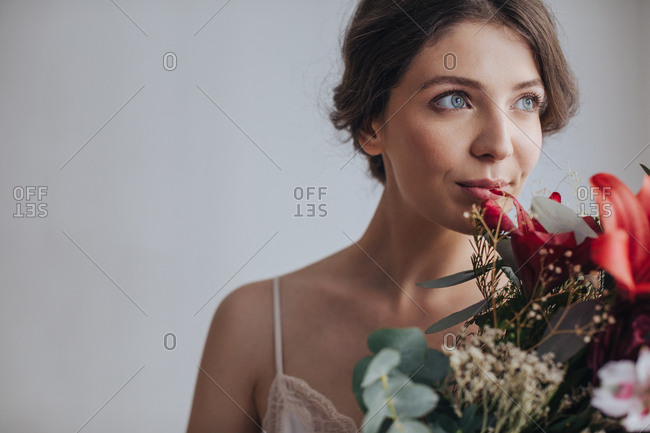 Portrait of beautiful dreamy young blue-eyed woman holding bouquet and smelling flowers.