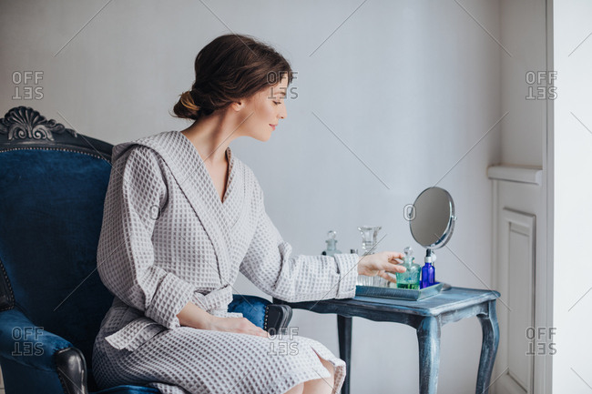 Beautiful Caucasian woman in bathrobe sitting at luxury spa salon and  holding cosmetic serum bottle.