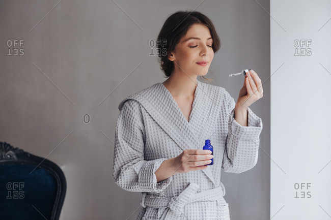 Beautiful Caucasian young woman holding cosmetic serum and smelling pipette.