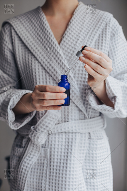Hands of unrecognizable woman in bathrobe holding bottle of cosmetic serum and a pipette.