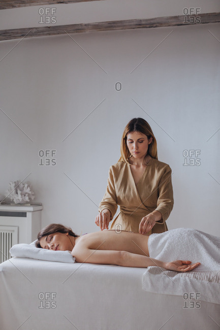 Pretty Caucasian woman masseuse putting therapy crystals on woman's back.