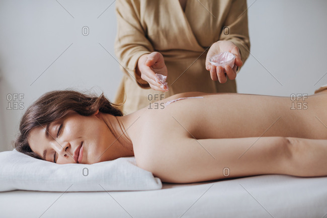 A masseuse putting natural moisturizing cosmetic cream on woman's back at spa salon.