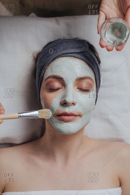 Pretty woman enjoying beauty mask treatment at spa salon.