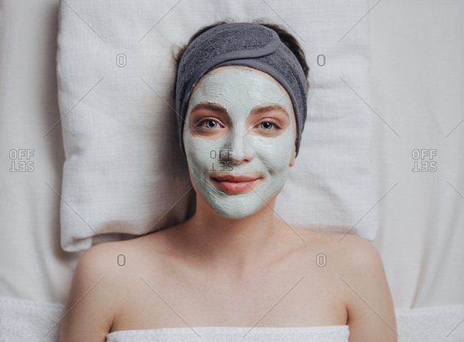 Portrait of pretty Caucasian woman laying at spa salon with cosmetic mask on her face and looking at camera.