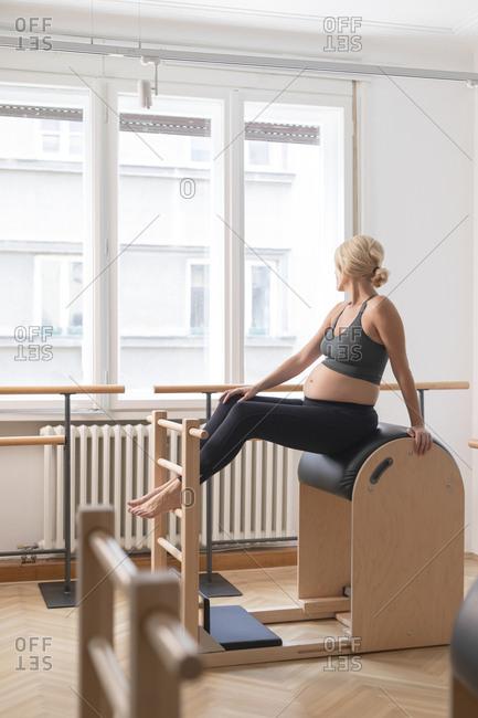 Pregnant woman in sportswear sitting at fitness studio.