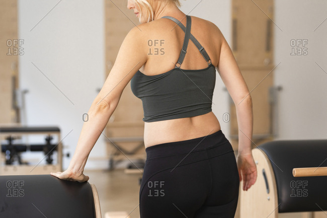Back view of a woman in sportswear standing at fitness studio.