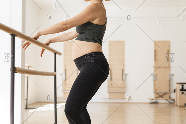 Anonymous pregnant woman in sportswear doing pilates exercise on a barre.
